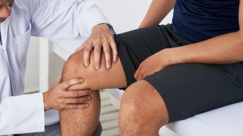 Chiropractor examining knee