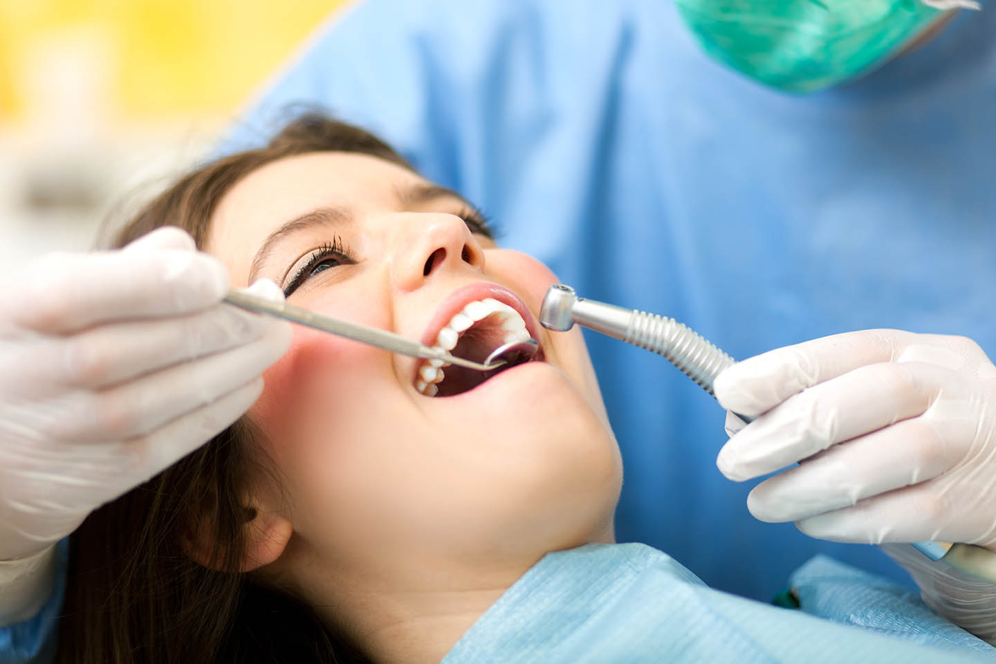 Young woman receiving teeth cleaning