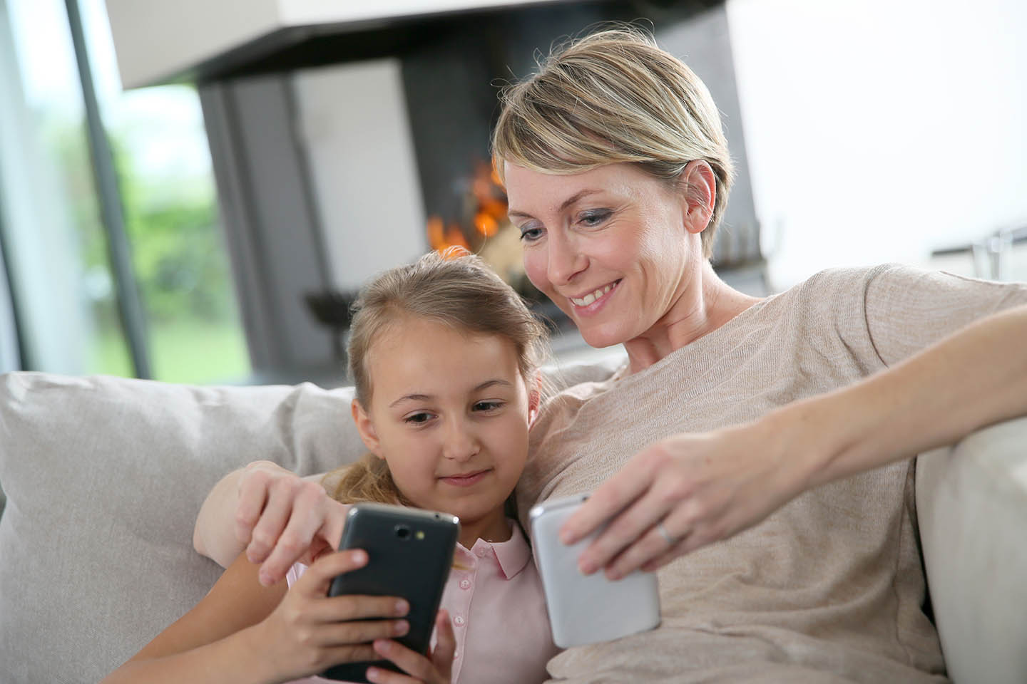 Mother and daughter smiling at smartphone