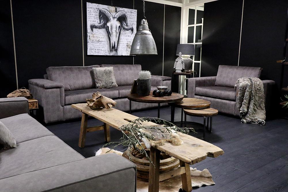 Complete landelijke woonkamer met stoffen banken en fauteuil en houten tafels, aangekleed met sfeervolle landelijke accessoires.