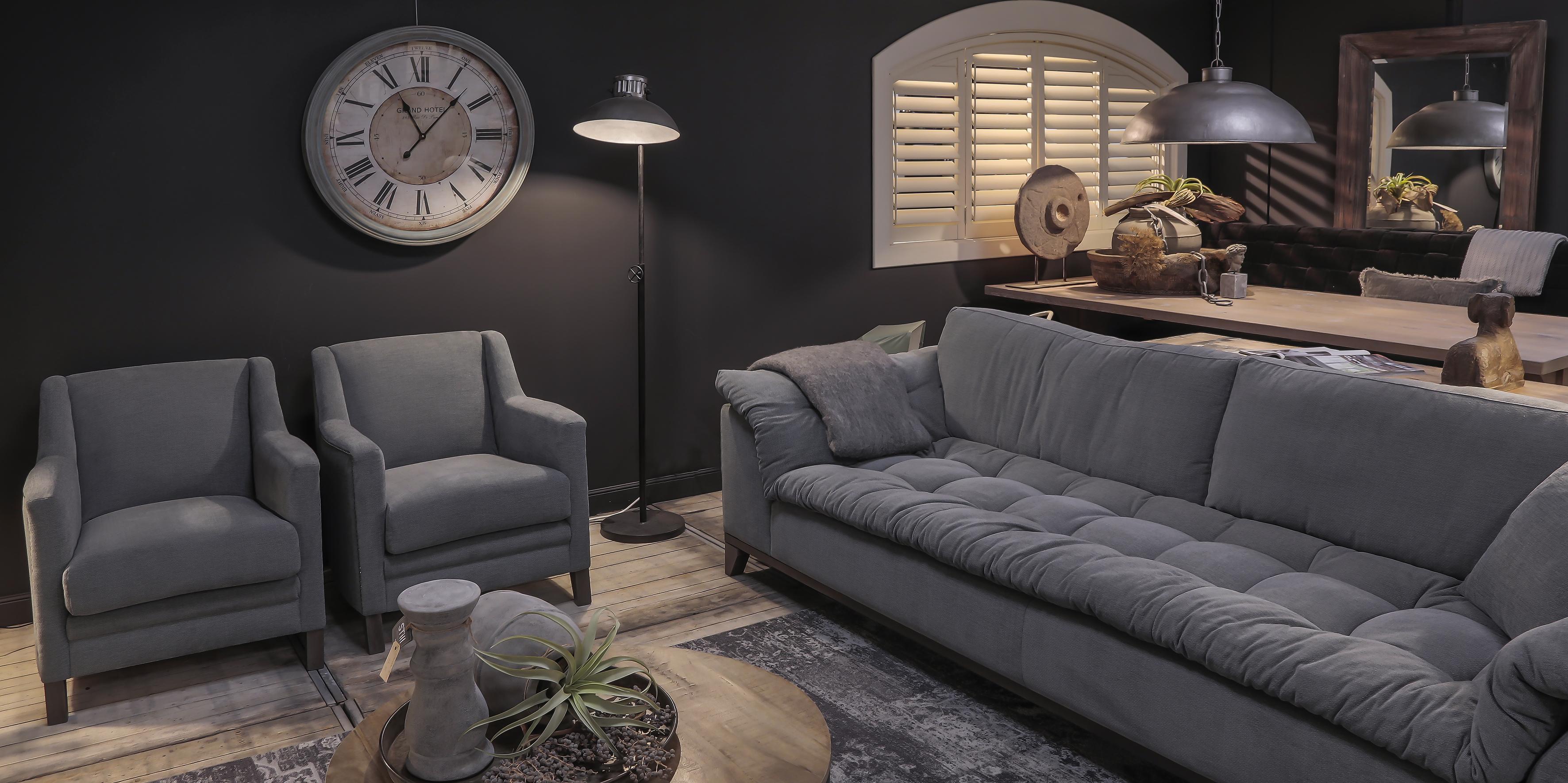 Landelijke woonkamer inrichting met ronde salontafel, set grijze fauteuils en een landelijke stoffen bank.