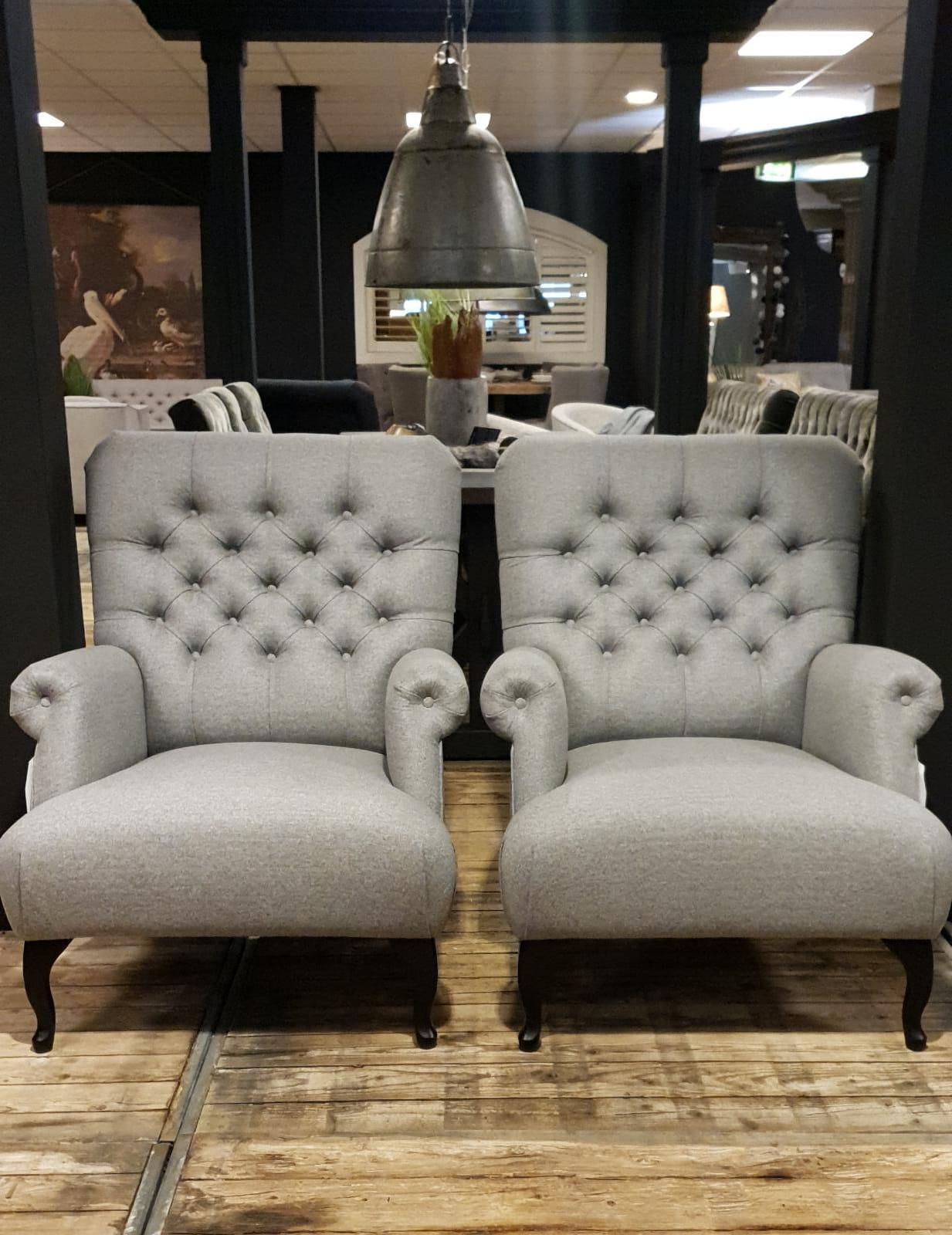 Landelijke zitmeubelen met knopen. Gecapitonneerde grijze fauteuils van stof.