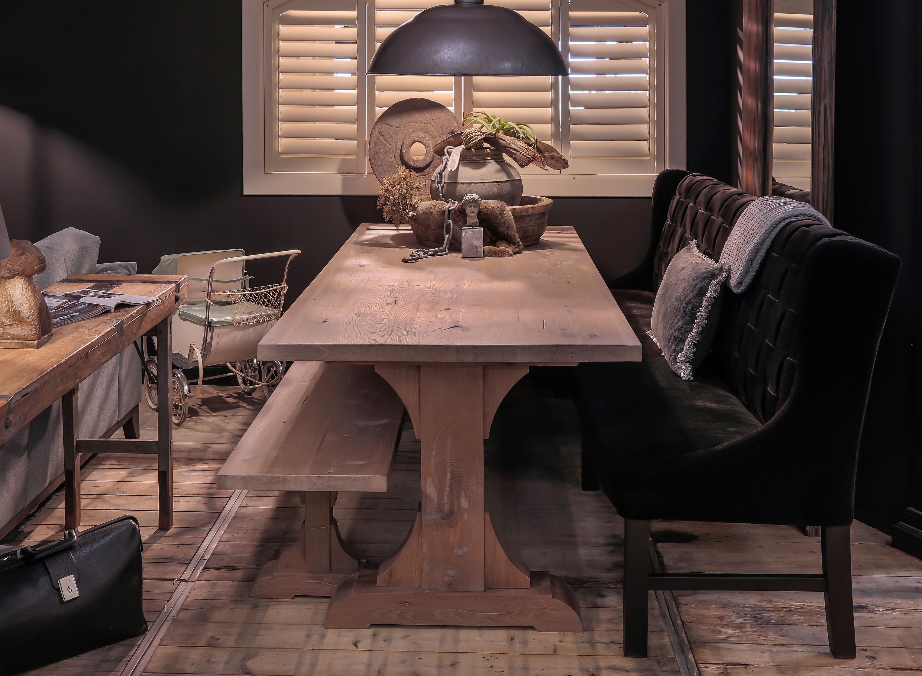 Landelijke eettafel van hout met een fluweel eetbank. Op tafel staan landelijk accessoires.