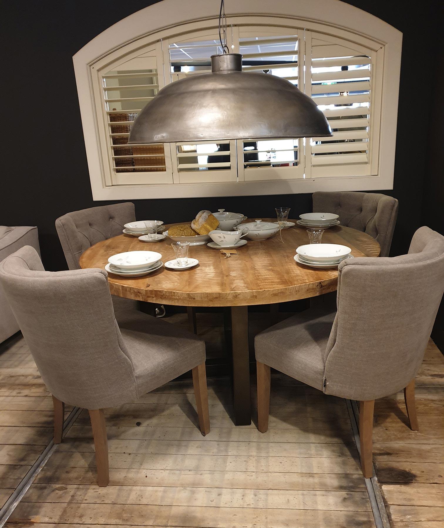 Landelijke eettafels met stoelen. Houten ronde eetkamertafel. Stoffen klassieke eetstoelen.