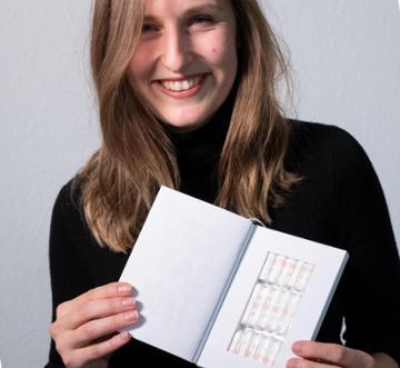 """Ann-Sophie-Claus, eine der Gründerinnen der Firma """"The Female Company"""", hält das von der Firma entwickelte """"Tampon Book"""" in den Händen; Foto: picture alliance/Bernd Weissbrod/dpa"""