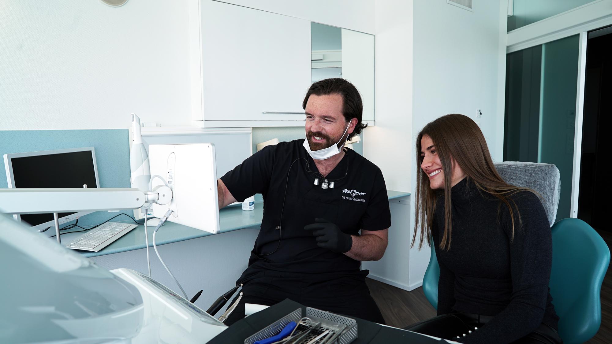 Dr. Markus Franke, der Zahnarztpraxis Resident, zeigt einer Kundin einen 3D-Scan ihres Mundes.