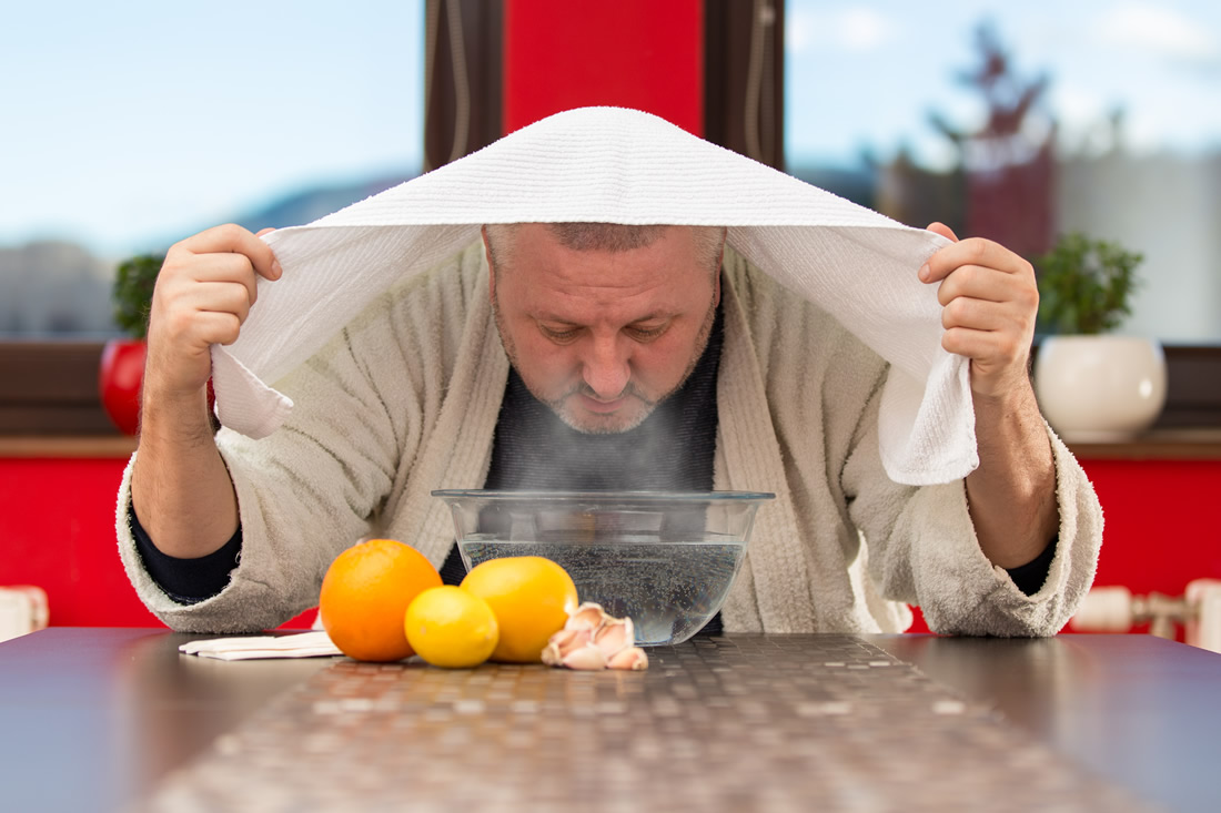 Man breathes in steam from a bowl to help cure his sinus infection