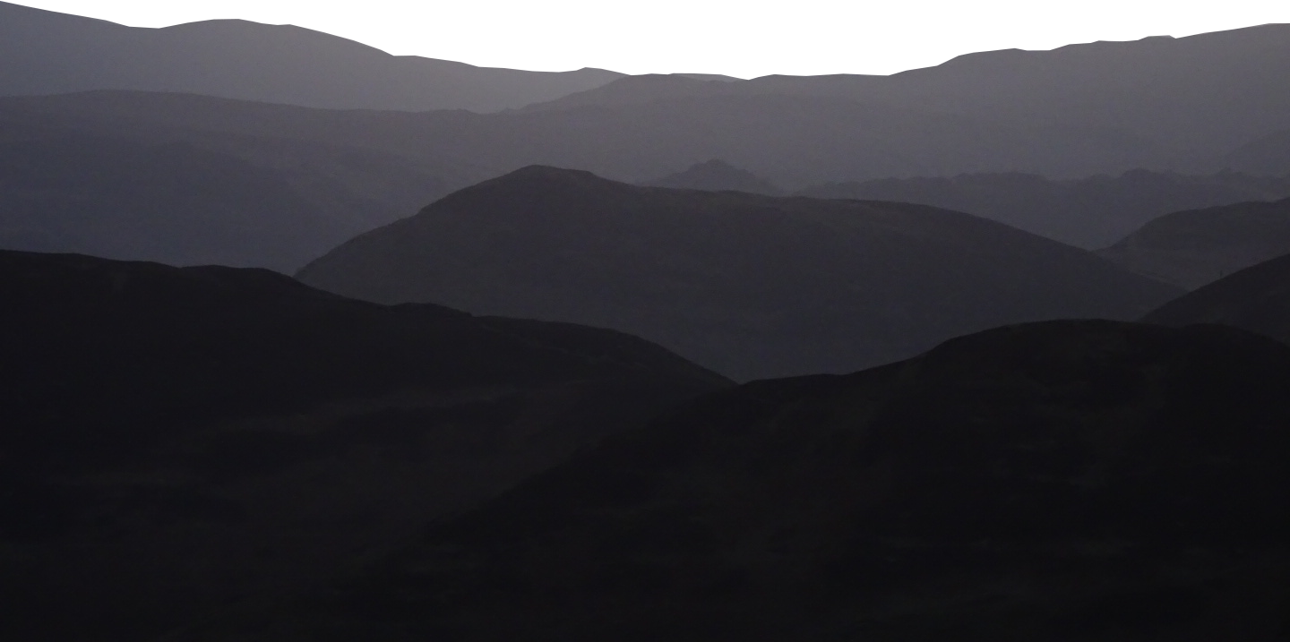 Silhouetted layered landscape of Lake District mountains graduating from dark to light grey