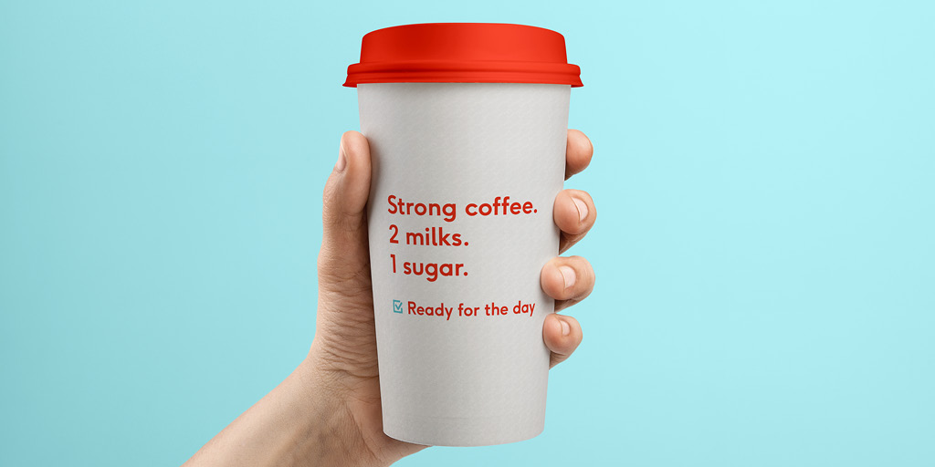 "A person holding a cup of coffee with a red lid. On the cup, in red text it reads ""Strong coffee. 2 milks. 1 sugar. Checkmark, Ready for the day."""