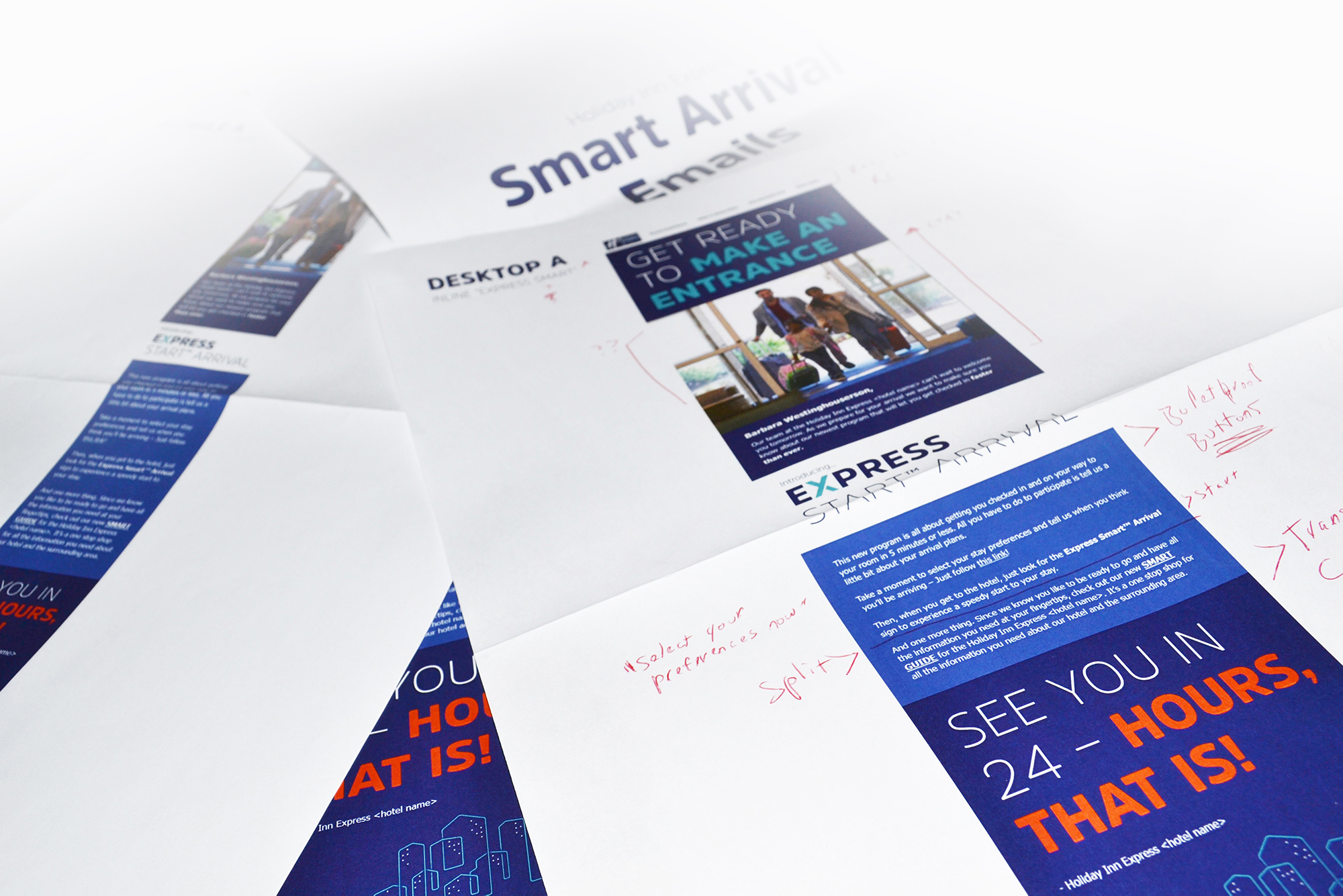 An image of printed out iterations of the smart guide piled on top of one-another with revision notes on them in red ink