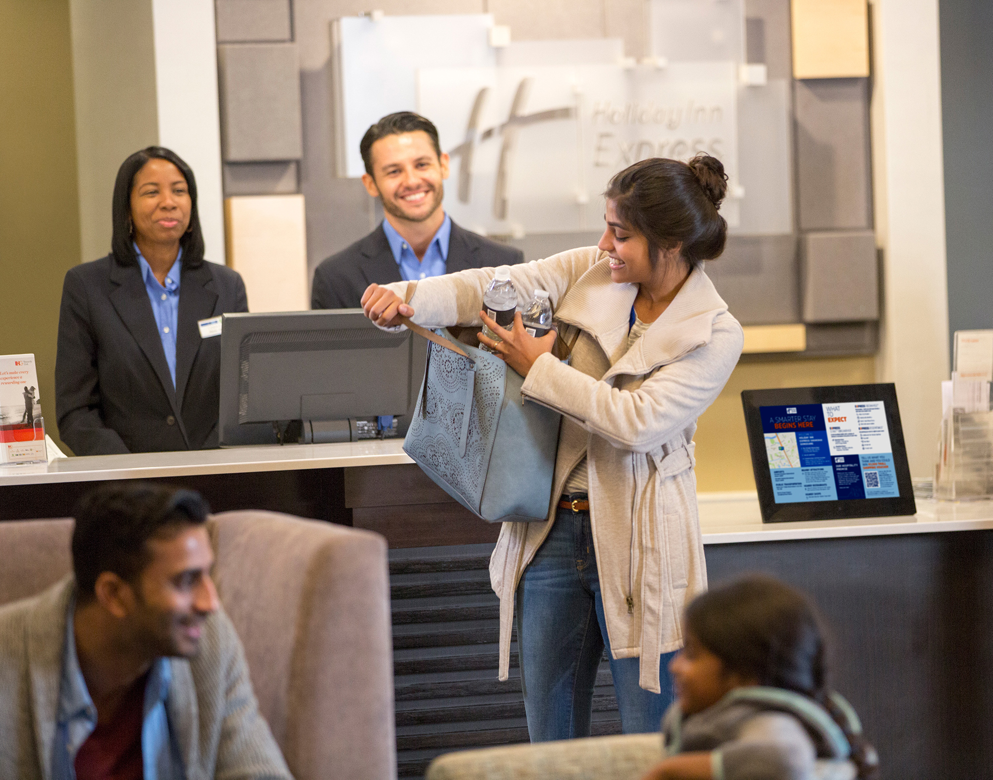 A guest at a hotel checkin reaching into her purse. On the table in front of her is a screen with the smart guide on it, with blue and white sections detailing relevant information for the guests stay