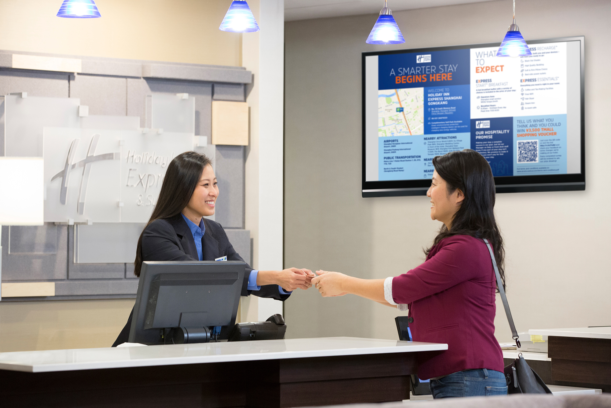 A guest shaking hands with a desk clerk at a hotel. On the wall next to her is a television with the smart guide on it, with blue and white sections detailing relevant information for the guests stay