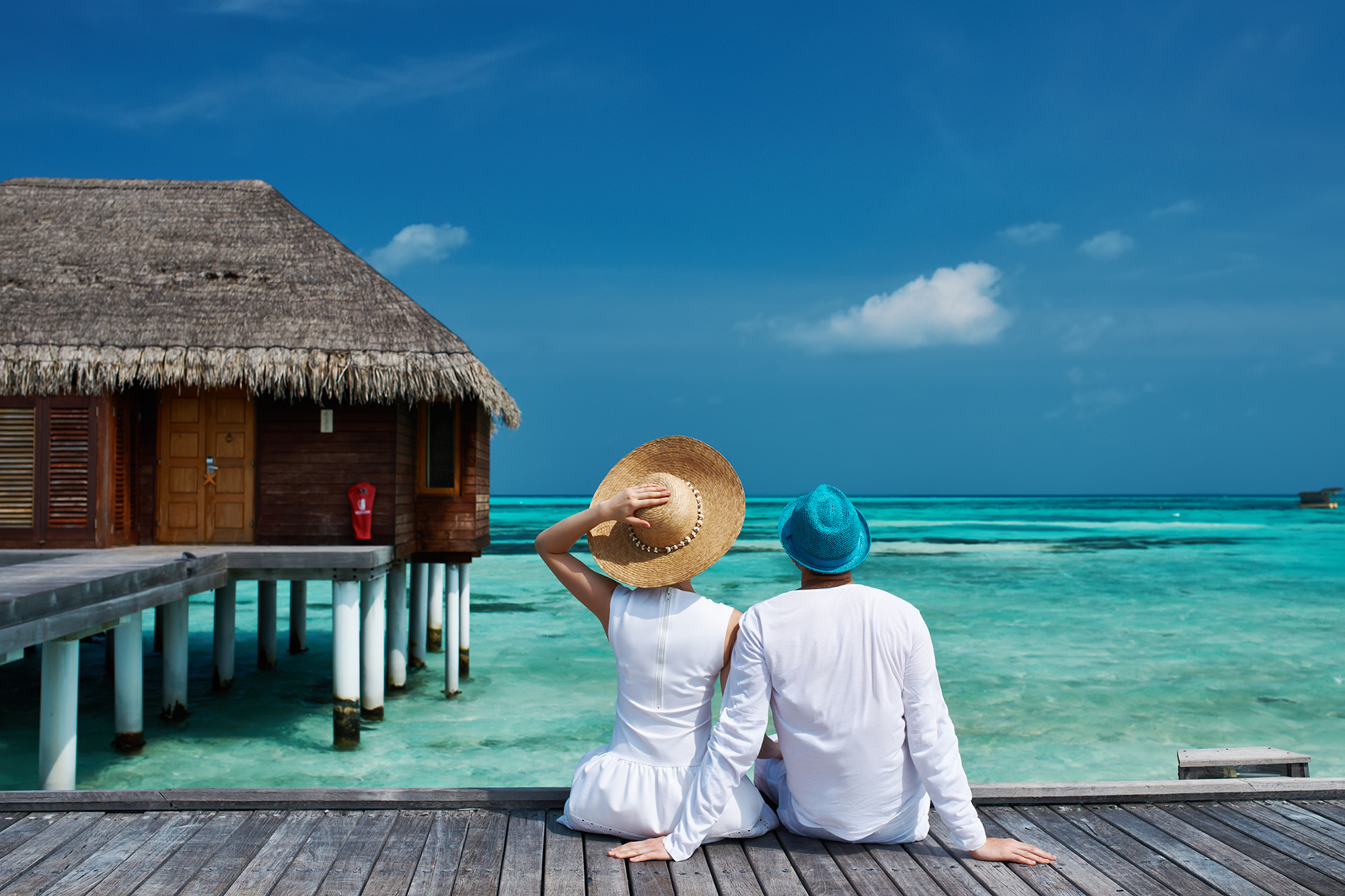 A man and a woman sitting on a pier next to a straw hut, looking out onto a beautiful blue ocean in from of them underneath a bright blue sky. This is an image we used in the campaign