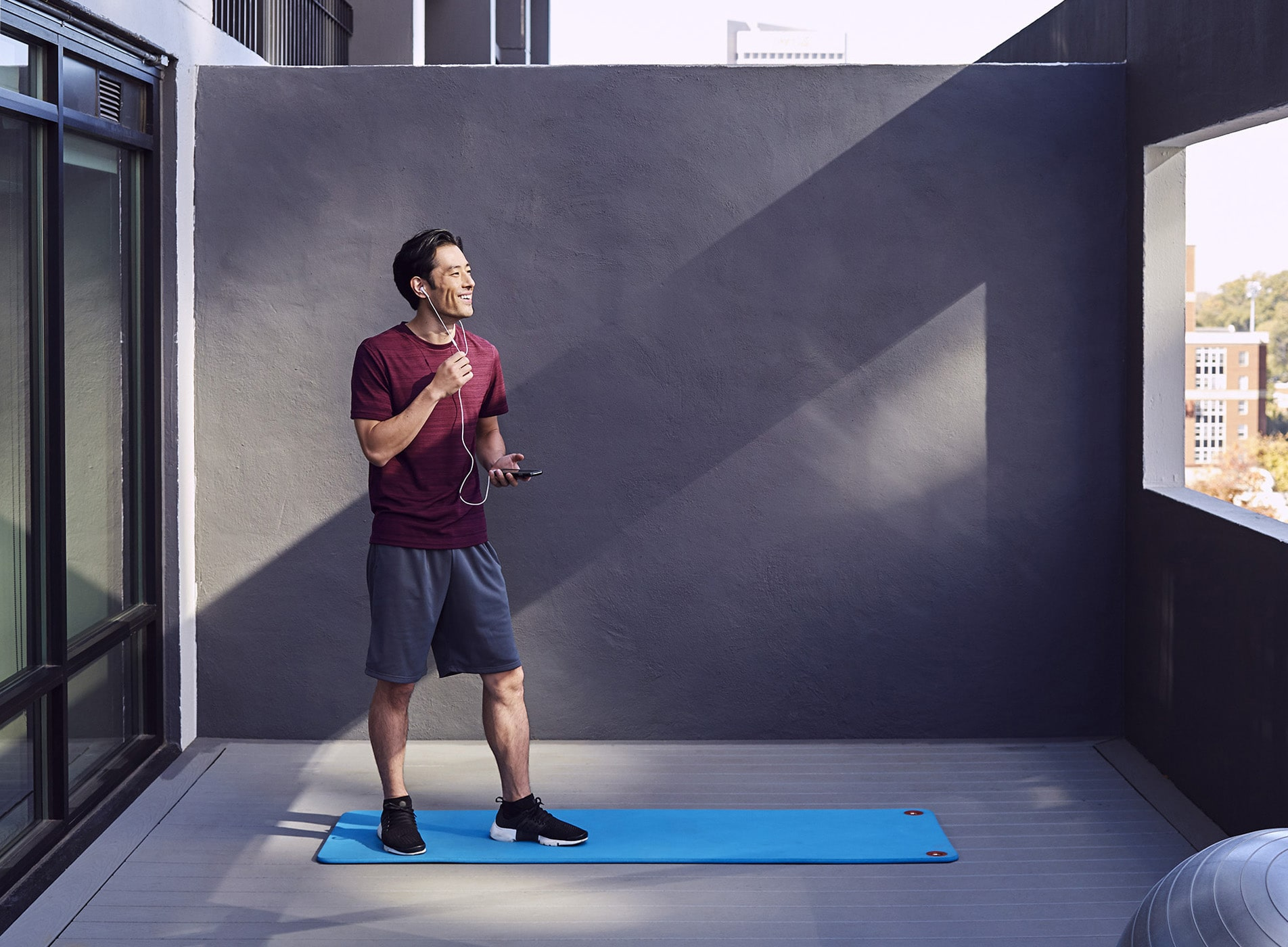 A man on the patio of a hotel room doing yoga on a blue mat while also talking on the phone.