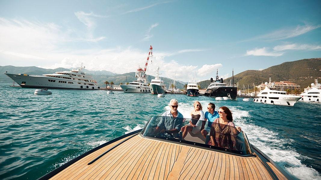 Happy, wealthy people on a speedboat in Porto Montenegro