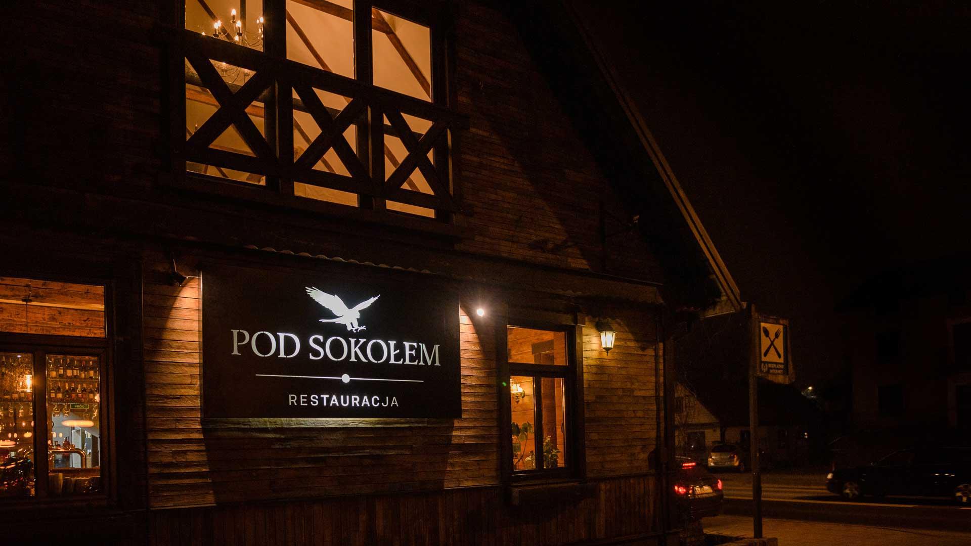 front restauracji wieczorem z podświetlonym logo