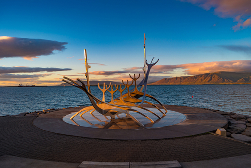Cityscape over Reykjavik business and touristic downtown, embankment, ocean, harbor, modern buildings and monument of Viking boat Sun Voyager at sunset skyline