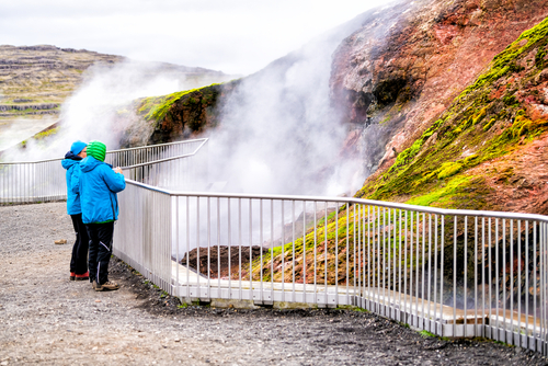 Deildartunguhver, Iceland - June 18, 2018 Hot springs and people looking at hot water outside in summer with vapor steam rising from cave