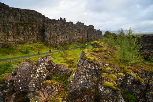 Tourists walking among the tectonic landforms of Þingvellir (Thingvellir) National Park, Iceland
