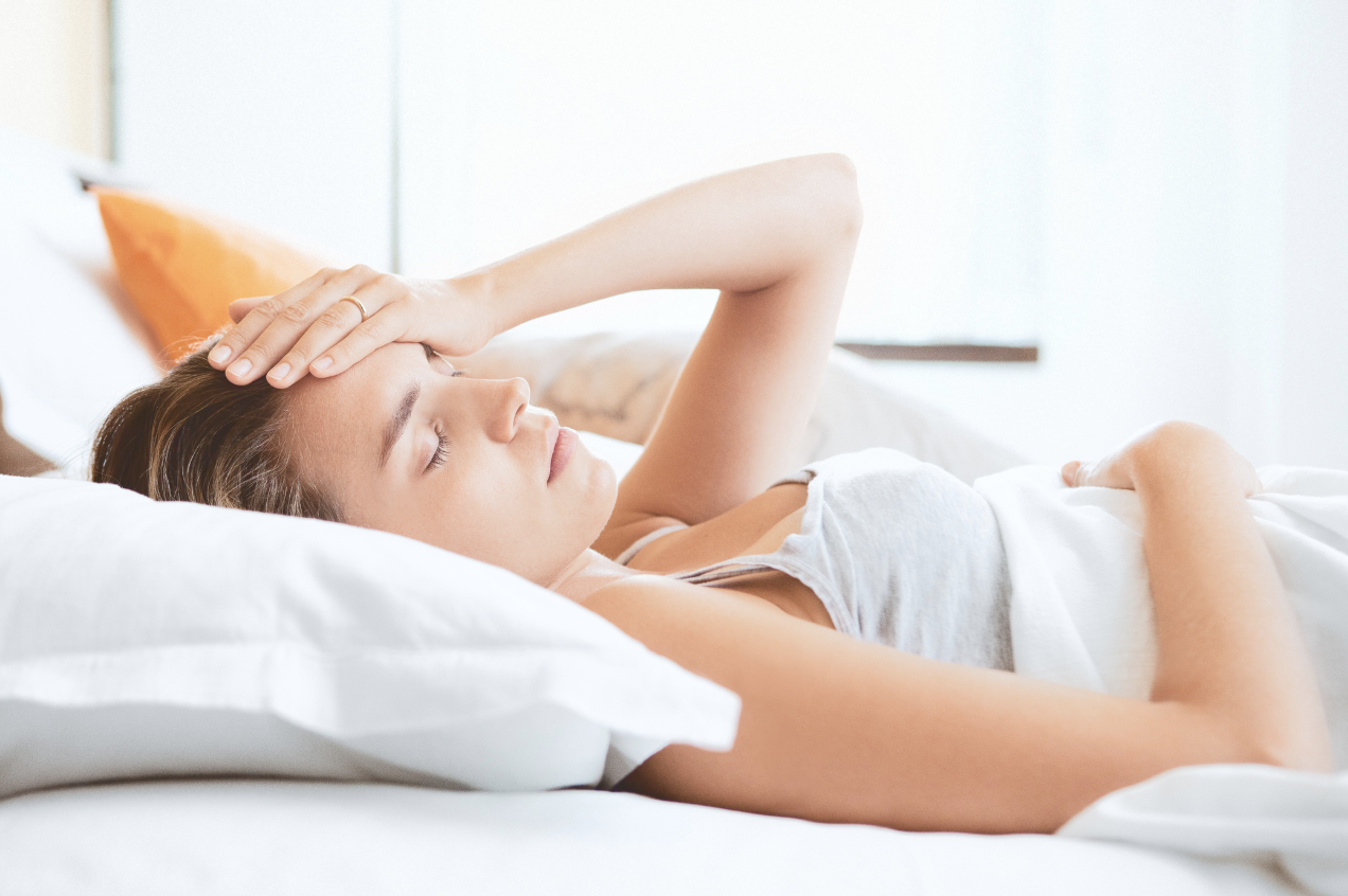 woman bed hand on forehead