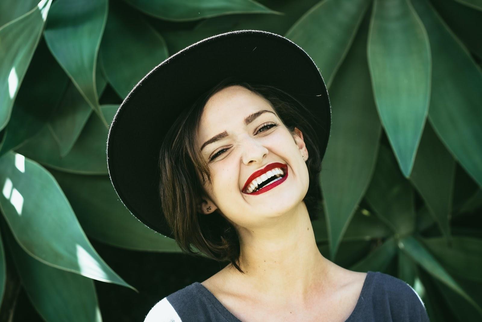 smiling brunette woman wearing a black hat