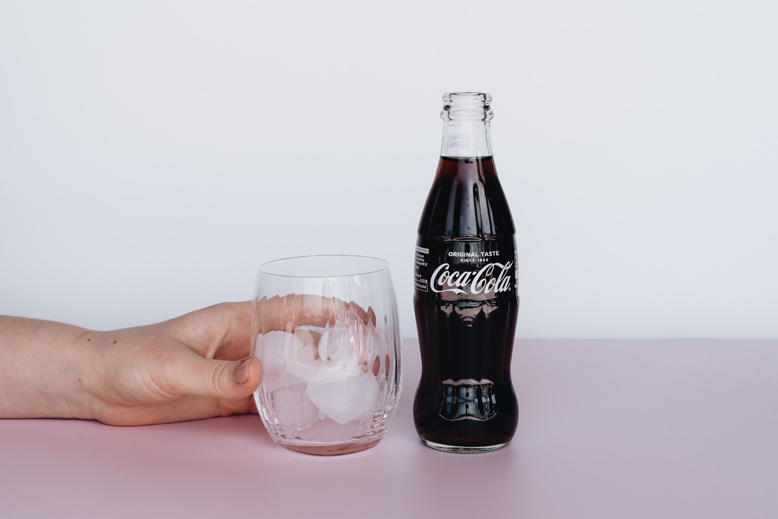 bottle of coca cola next to glass