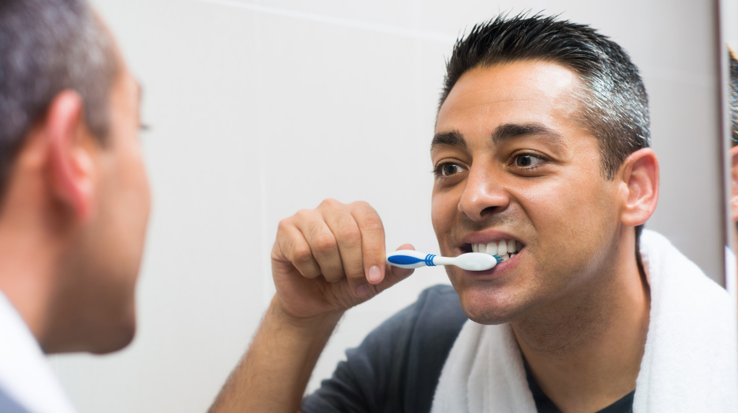 man brushing teeth in mirror