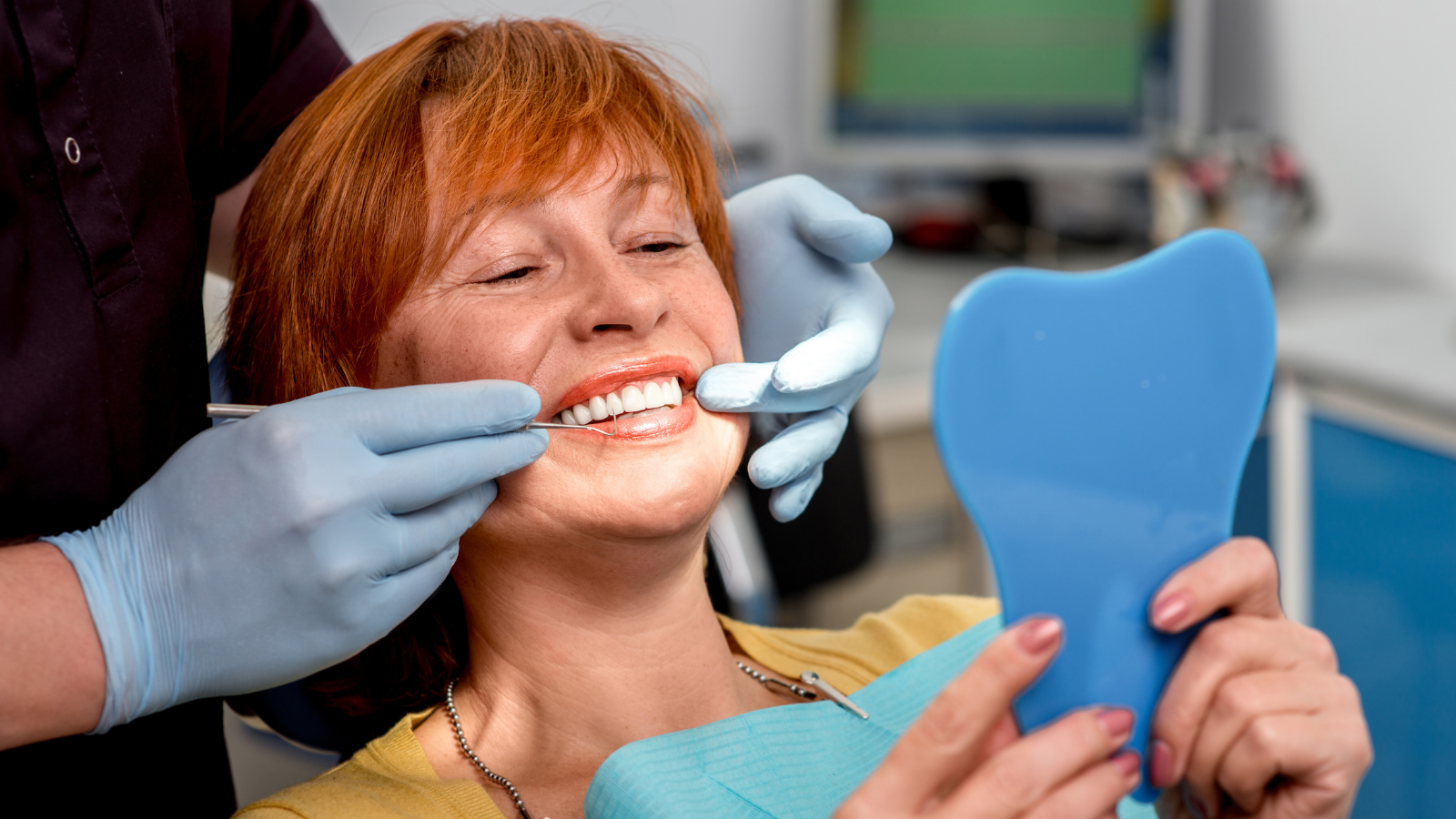 woman checking dentures in dentists office
