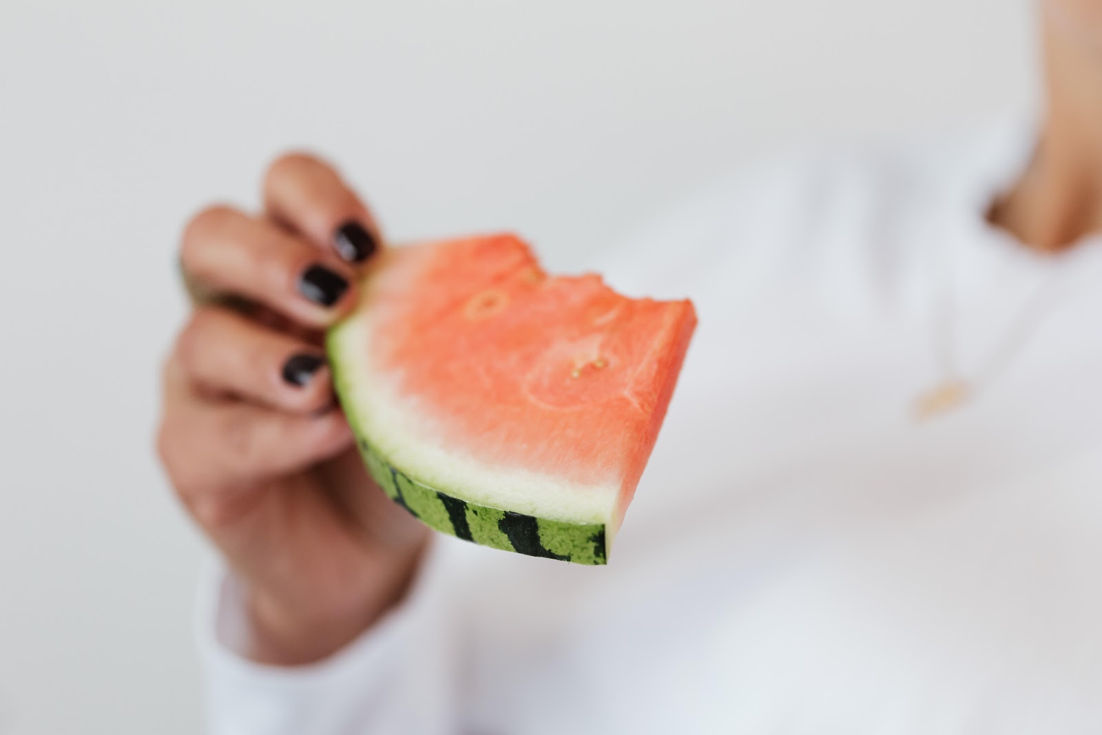 woman eating piece of watermelon