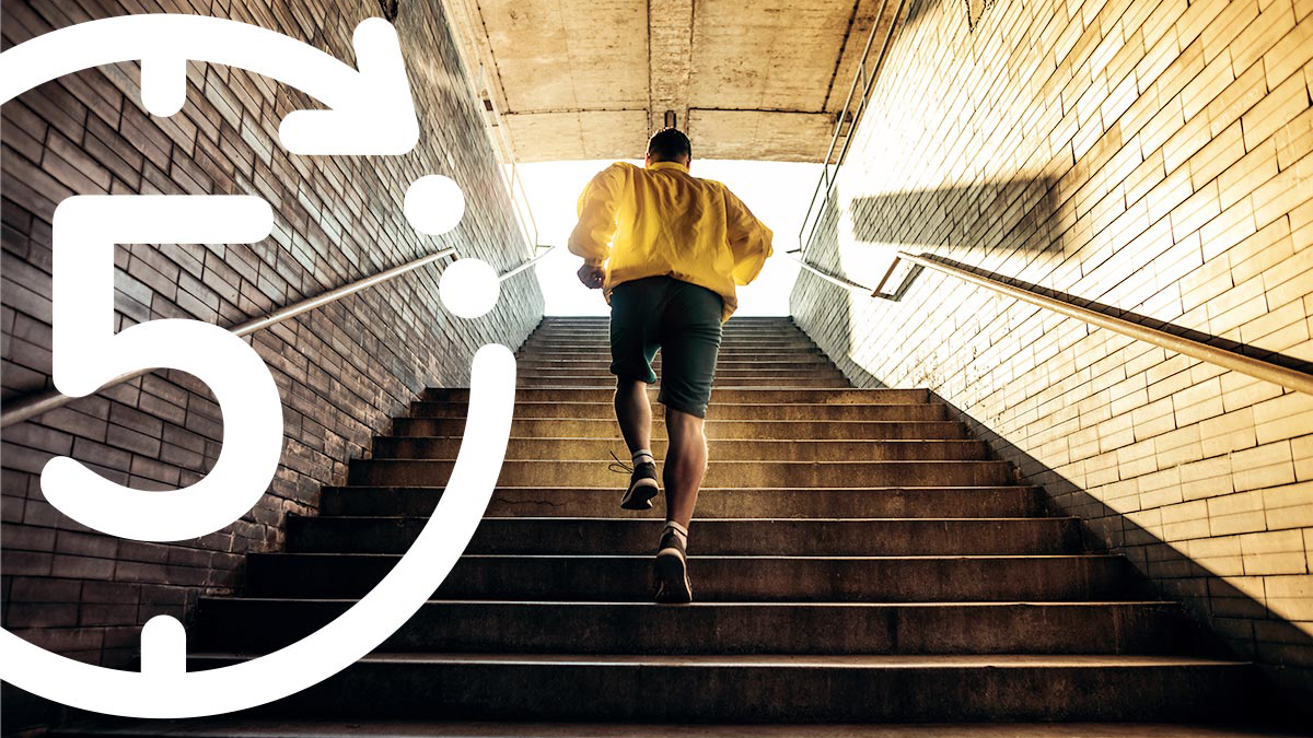 "Photo of a man in a yellow jacket and gray shorts running up a flight of stairs from underground into sunlight and a large number ""5"" inside a circle superimposed on the image"