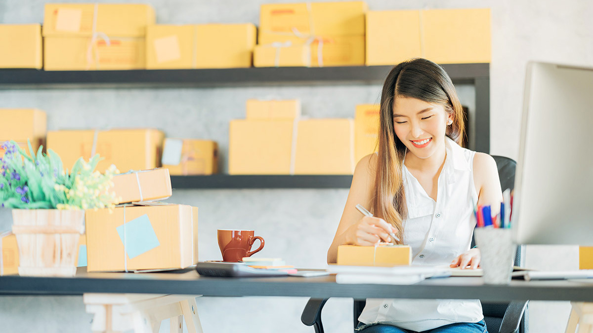 Photo of a businesswoman sitting in front of shipping boxes