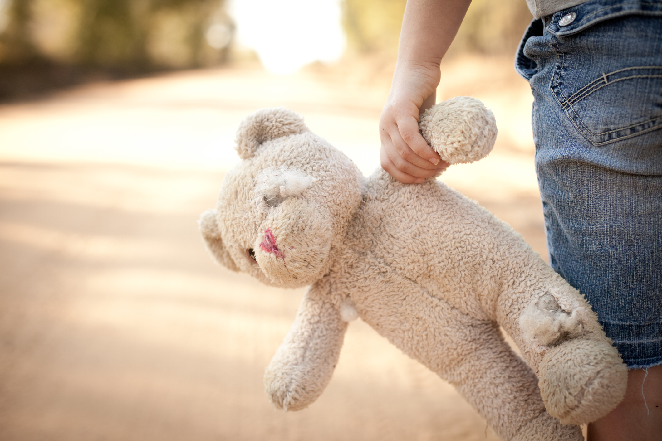 photo of child holding tattered teddy bear