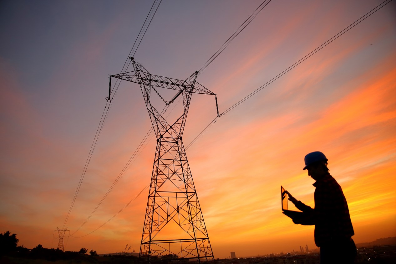 photo of a man checking laptop near a power line
