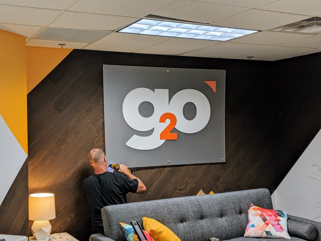 Photo of man hanging up the new g2o sign in the lobby