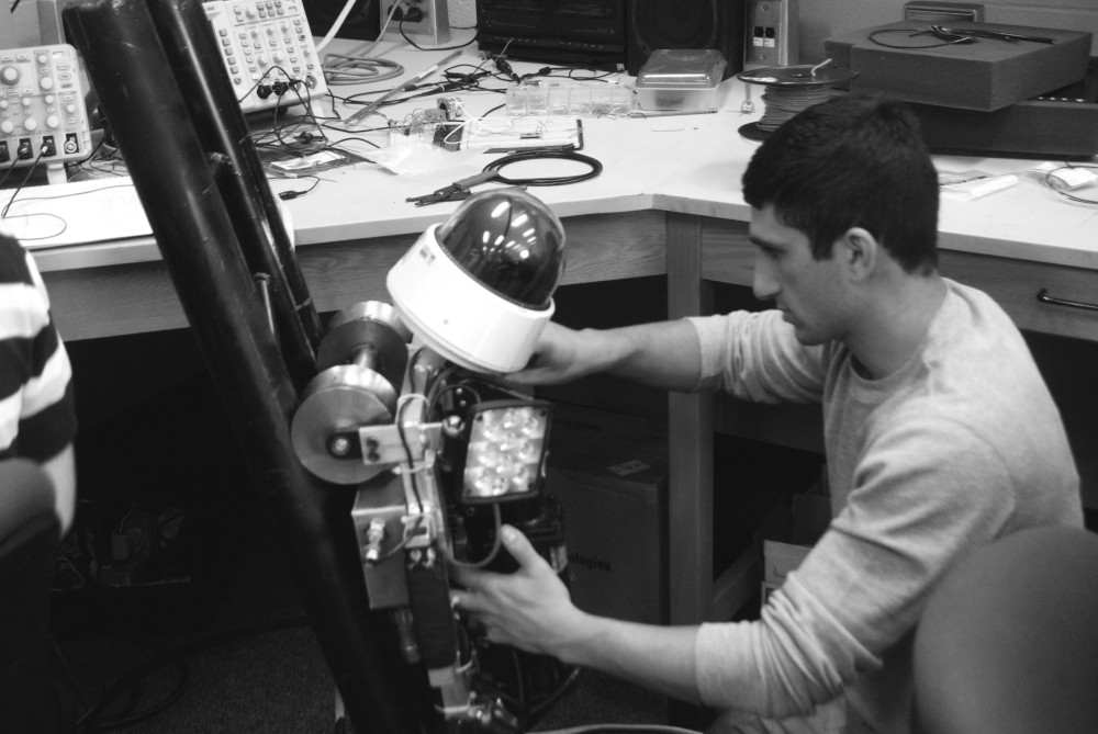 Jake Loosararian with early robot prototype