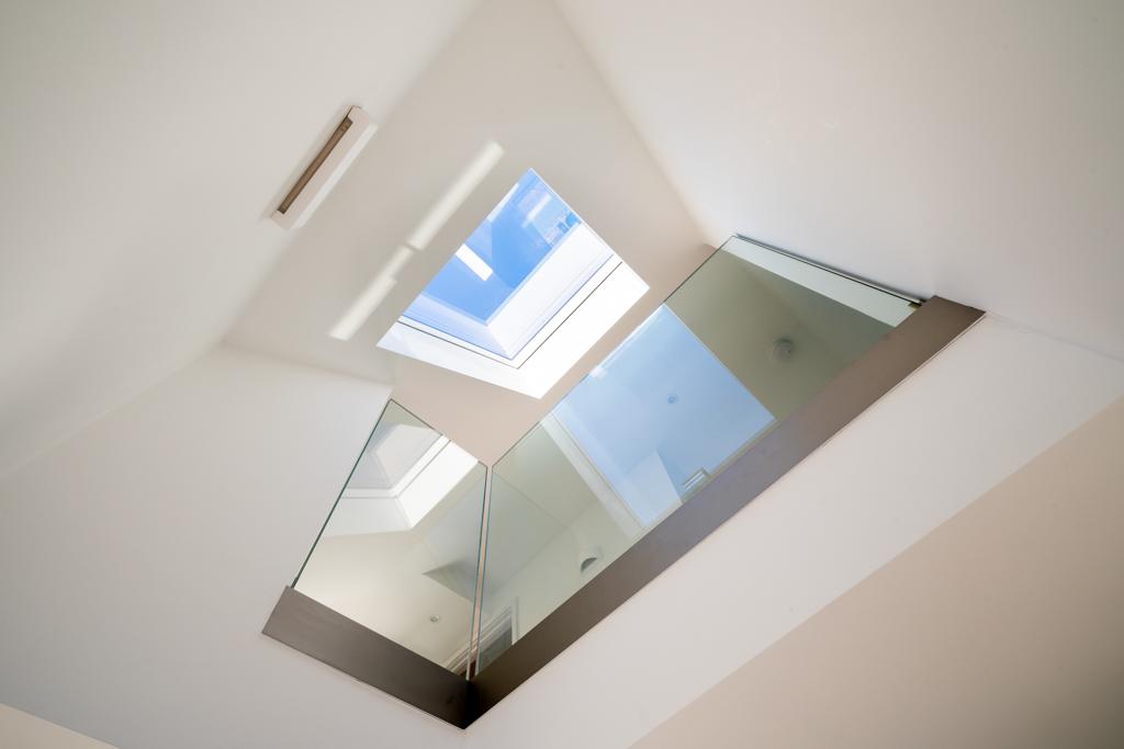 Interior of velux roof light over mezzanine with glass balcony