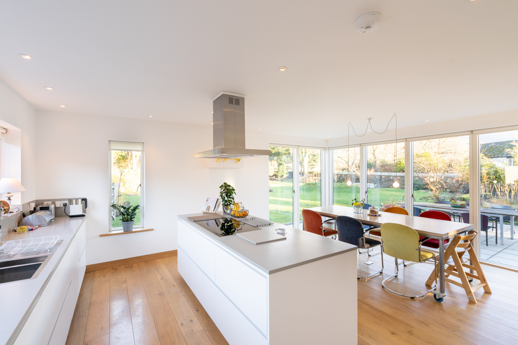 Contemporary kitchen with glazing both sides giving contact with rear terrace and garden