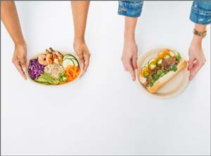 Two people placing their lunch down on a table
