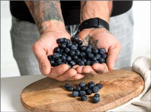 A person holding a handful of blueberries