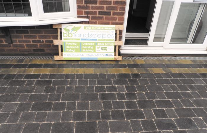 Charcoal Rumbled paving set driveway with a triple border using burnt willow, inset manhole tray, K.L kerb set planter and an ACO channel drainage system.