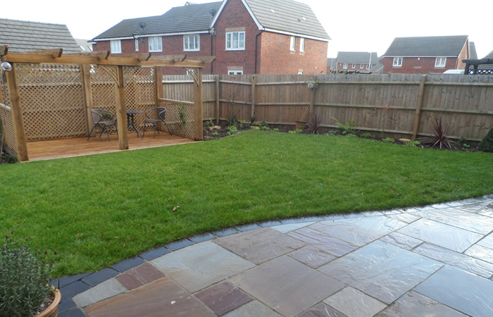 Mixed size camal natural stone patio with large charcoal rumbled block, new lawn edged with rumbled block border and bespoke pergola seating area.