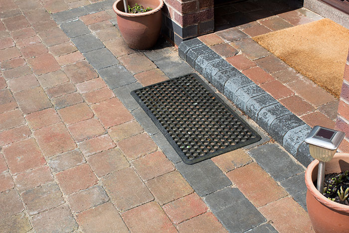Autumn mix Rumbled paving set driveway with triple border in charcoal, raised planter using K.S kerb sets, ACO channel drainage system installed and new iron gates.