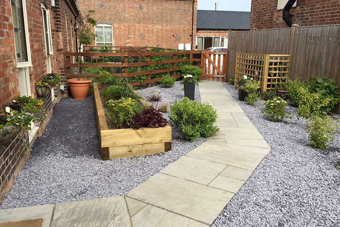 Raj sawn edge natural stone patio and Raj circle, sleeper planters and finished with plum slate.