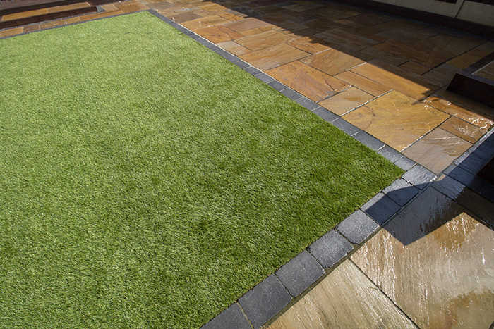 Mixed size camal natural stone patio with large charcoal rumbled block, raised sleeper area and artificial grass lawn.
