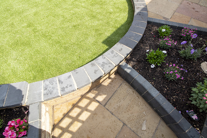 Three level camal natural stone patio with large charcoal rumbled block, steps built from charcoal kerbs, mellow York abbey walling containing a bedding area and artificial grass.