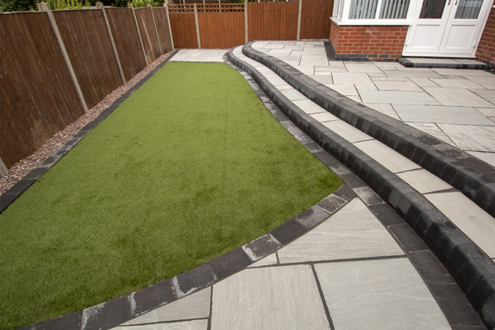 Three level Mixed size grey natural stone patio with charcoal rumbled block, steps built from kerbs and artificial grass area.