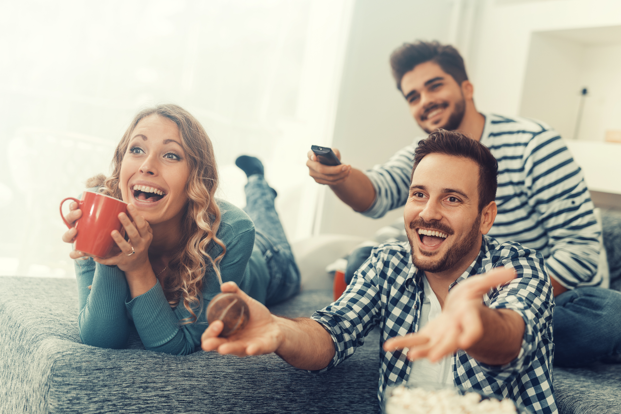 Group of friends smiling and watching television together.