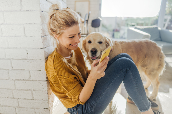 Young adult female using a mobile device with her happy dog.
