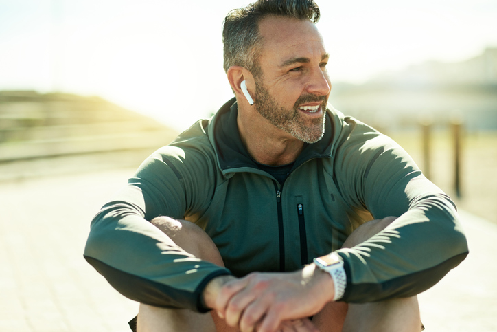 Man takes a break from working out to listen to his favorite podcast through his wireless earbuds