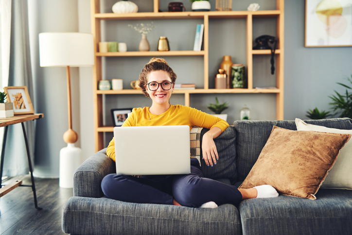 Woman smiling, sitting on her couch using her laptop